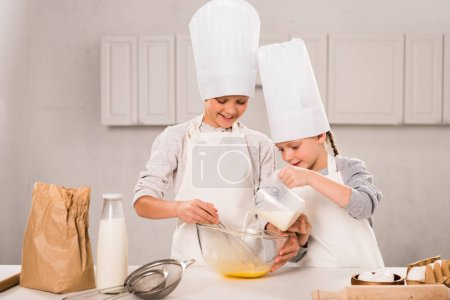 Photo for Kid pouring milk into bowl while brother whisking at table in kitchen - Royalty Free Image