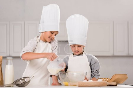 Photo for Boy pouring milk into bowl while sister standing near at table in kitchen - Royalty Free Image