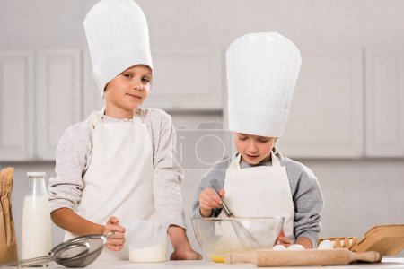 little boy looking at camera and his sister whisking eggs in bowl at table in kitchen