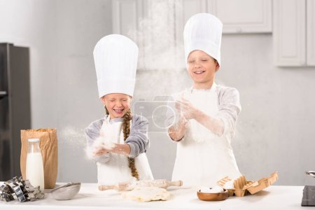 selective focus of happy children in chef hats having fun with flour in kitchen