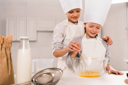 Photo for Boy with sister in chef hats whisking eggs in bowl at table in kitchen - Royalty Free Image