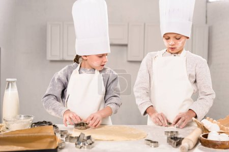 Photo for Selective focus of little brother and sister in chef hats and aprons cutting out dough for cookies at table in kitchen - Royalty Free Image