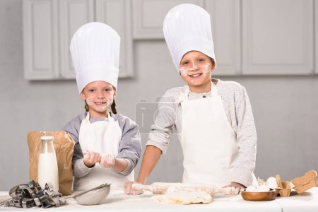 sister and brother in chef hats having fun with flour at table in kitchen