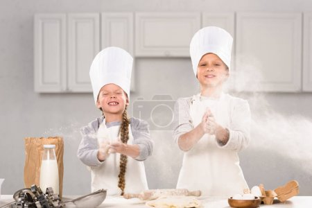 Photo for Little happy children in chef hats having fun with flour in kitchen - Royalty Free Image