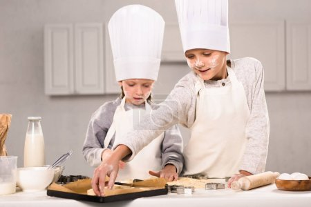 adorable sister and her brother putting dough for cookies on baking tray in kitchen