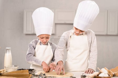 adorable little brother and sister in chef hats and aprons cutting out dough for cookies at table in kitchen