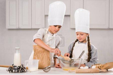 frère et sœur dans toques et tabliers en fouettant les oeufs dans un bol à table dans la cuisine