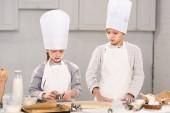"""Постер, картина, фотообои """"сестра и брат шеф-повар шляпы и фартуки, вырезая тесто для печенья на столе в кухне"""""""