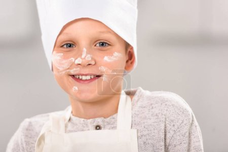 close up portrait of happy boy with flour on face in chef hat looking at camera