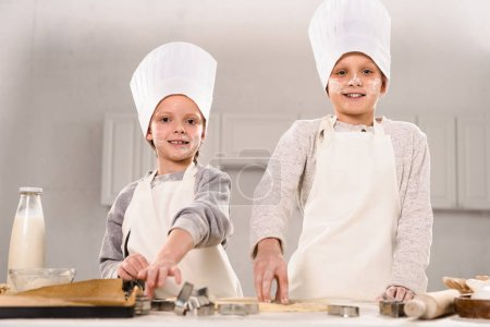 Photo for Happy children in chef hats and aprons cutting out dough for cookies at table in kitchen - Royalty Free Image