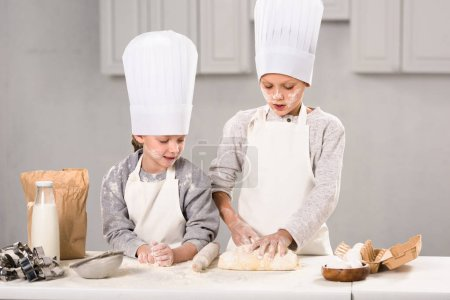 children in aprons and chef hats making dough with rolling pin at table in kitchen