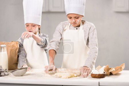 Photo for Selective focus of brother and sister in aprons and chef hats making dough with rolling pin at table in kitchen - Royalty Free Image