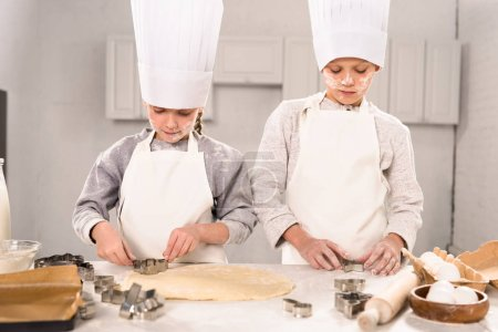 little brother and sister in chef hats and aprons cutting out dough for cookies at table in kitchen