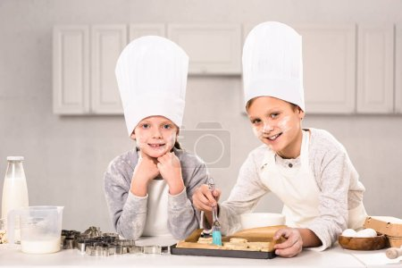 joyful children in aprons brushing cookies on baking tray in kitchen