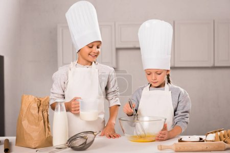 Photo for Brother and sister in chef hats and aprons whisking eggs in bowl at table in kitchen - Royalty Free Image