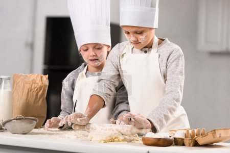 Photo for Selective focus of kids in aprons and chef hats making dough with rolling pin at table in kitchen - Royalty Free Image