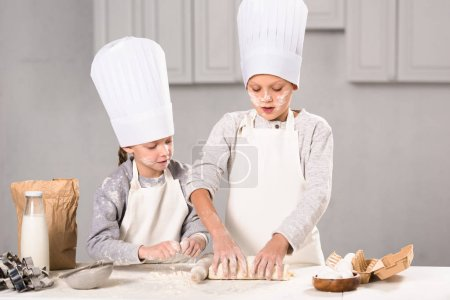 Photo for Focused kids in aprons and chef hats making dough with rolling pin at table in kitchen - Royalty Free Image