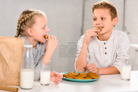 happy children eating cookies and drinking milk at table in kitchen