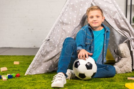 positive little boy sitting with soccer ball near tent at home