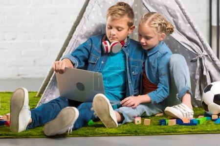 adorable petit frère et soeur avec ordinateur portable près de tente à la maison