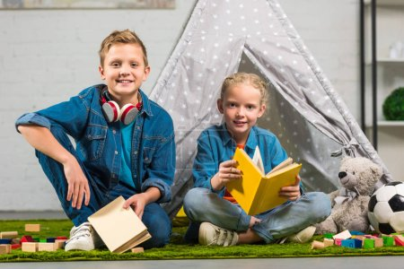 happy children with books looking at camera near tent at home