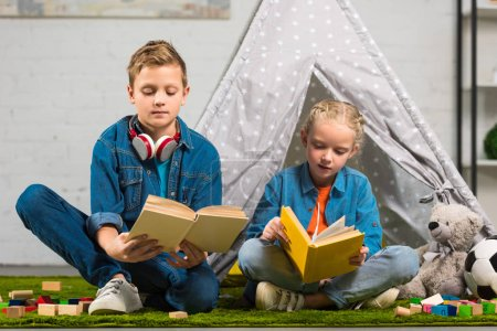 focused little sister and brother reading books near tent at home