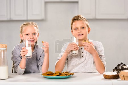 joyful children eating cookies and drinking milk at table in kitchen
