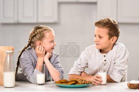 Photo pour Sourire les enfants regardent et assis à table avec les biscuits et le lait dans la cuisine - image libre de droit