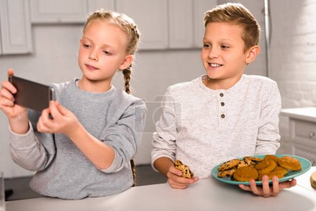 adorable child taking selfie on smartphone with brother holding plate with delicious cookies in kitchen
