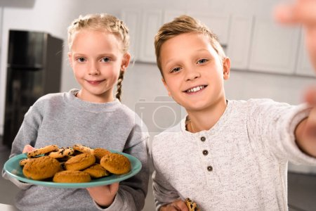 selective focus of boy taking selfie with sister while she holding plate with cookies