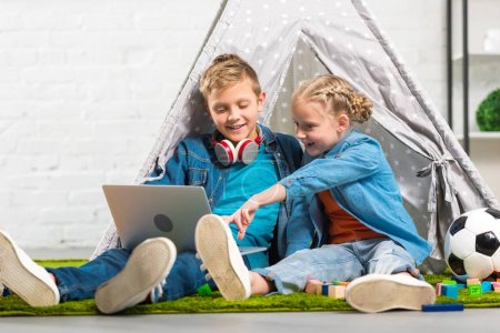child pointing at laptop screen to smiling brother with headphones over neck near tent at home