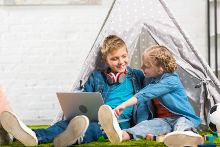 kid pointing at laptop screen to smiling brother with headphones over neck near tent at home