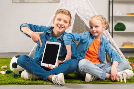 boy pointing at digital tablet with blank screen and his sister sitting near tent at home