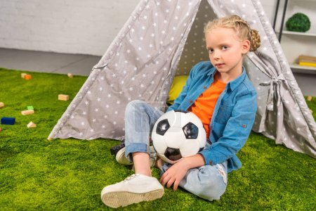 Photo for Kid with soccer ball looking at camera while sitting on green lawn near tent at home - Royalty Free Image