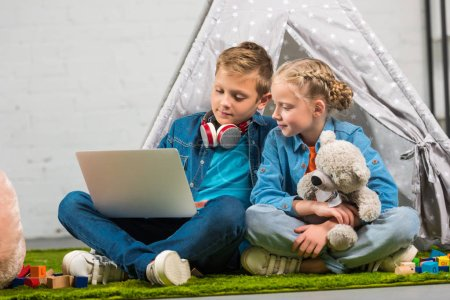 brother and sister with teddy bear and headphones using laptop near tent at home