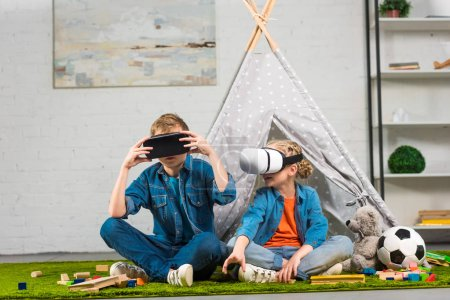brother and sister using virtual reality headsets near wigwam at home