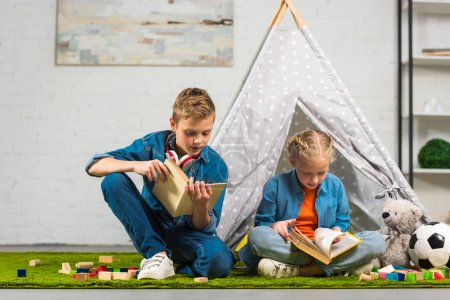 little sister and brother reading books near tent at home