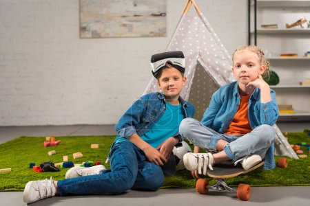 little boy with virtual reality headset over head and his sister sitting on skateboard near wigwam at home