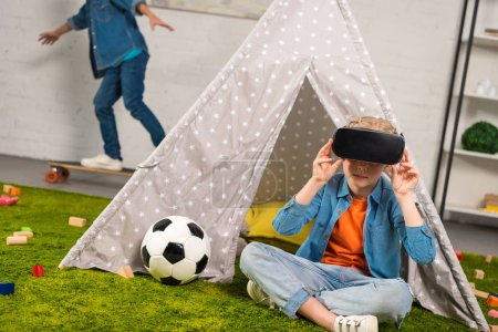 kid using virtual reality headset near wigwam while her brother riding on skateboard behind at home