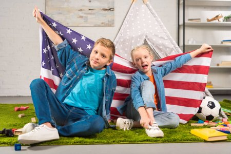 adorable kids showing national american flag near wigwam, independence day concept