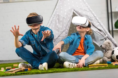 kids using virtual reality headsets and gesturing by hands near wigwam at home