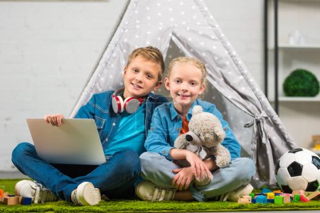 joyful children with laptop looking at camera and sitting with tent at home