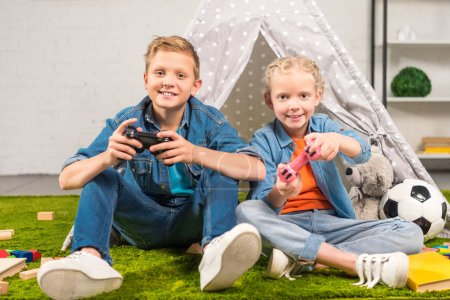Photo for Cheerful sister and brother playing with joysticks near wigwam at home - Royalty Free Image