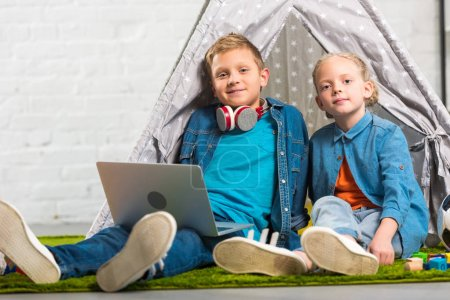 Photo for Happy little children with laptop looking at camera and sitting with tent at home - Royalty Free Image