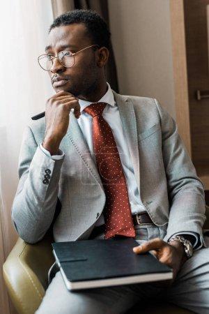 gentil homme d'affaires africain-américain en costume gris, assis dans le fauteuil avec le journal dans la chambre d'hôtel