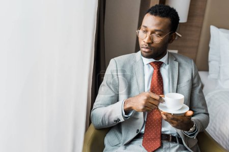 Photo for Serious african american businessman holding cup of coffee and looking at window - Royalty Free Image