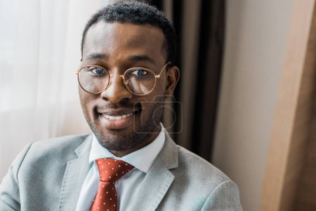 handsome smiling african american businessman in eyeglasses and gray jacket