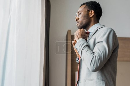 side view of african american businessman adjusting red tie and looking at window