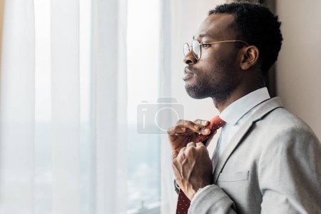 Photo for Profile portrait of african american businessman adjusting red tie and looking at window - Royalty Free Image
