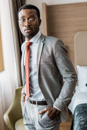 Photo for Handsome businessman in gray suit and red tie posing in hotel room - Royalty Free Image